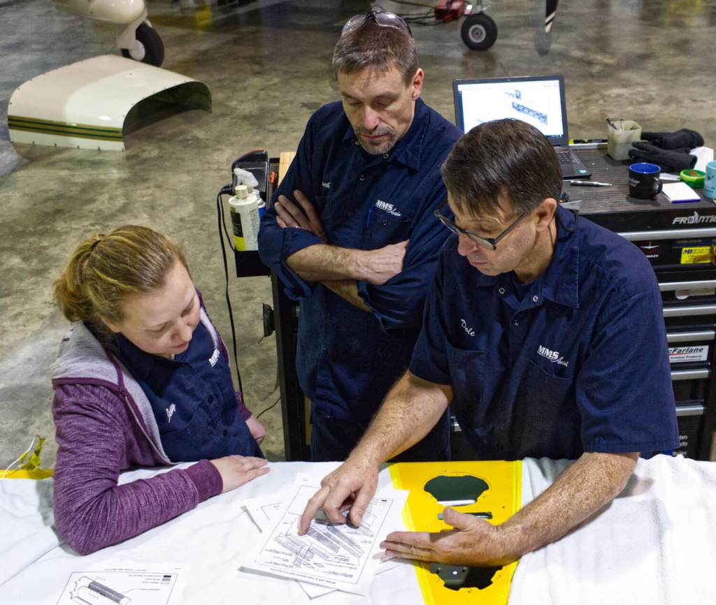 Discussing repair procedure at MMS Aviation for a Cessna 206 wing.